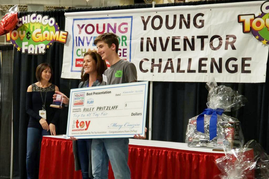 Getting the gold, sophomore Riley Pritzlaff is presented with a check that he won from the Young Inventors Challenge.