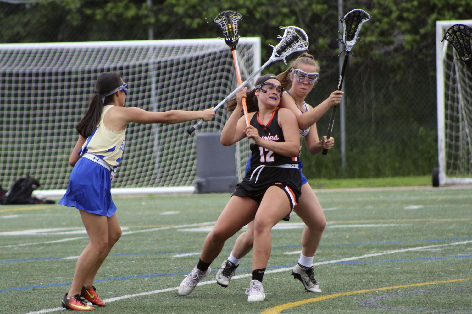 Junior Sarah McCallon pushes her way past an opposing team player to pass the ball during the 2018 lacrosse season. During the 2019 season the locker rooms will be under construction and spring sports need to find a place to change before practice.