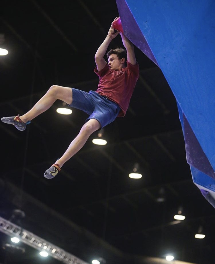 Squire dangles from a hold on one of the bouldering routes at the national competition. Photo provided by Brian Squire