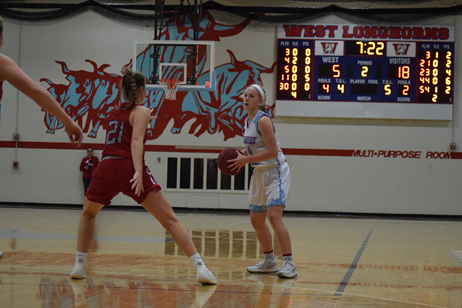 """Senior guard Tess Allgeyer stands at the top of the key and searches for a play to make. The team makes a point to learn from their losses and improve their strategy each game. """"We regularly reflect on our progress and talk about lessons learned from difficult losses, but also the wins.  If we continue to get better each day we play, we will be ready [for districts],"""" Boedecker said."""