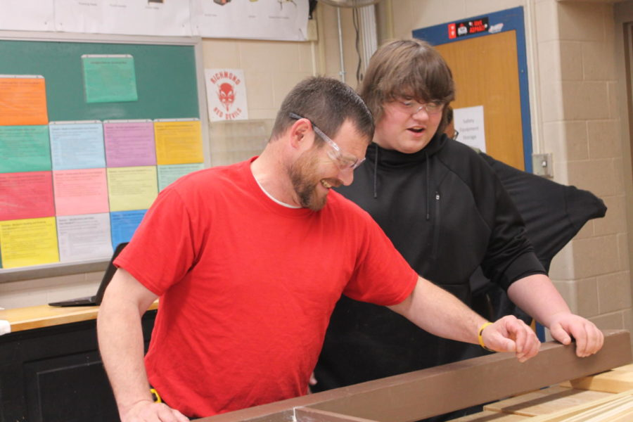 Going over build details, construction technology teacher Nathan Kendig (left) laughs after junior David Wysong makes a joke.