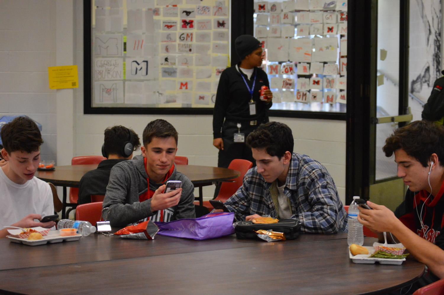 Sophomores (Left to right) Troup Jacobson, Hans Abruzzi, Evan Lankford, and Alex Hansen sit at the lunch table on their phones without interacting. This is a common scene among sophomores.