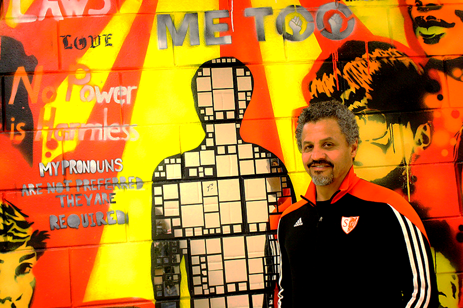"""Above is Mr. Aponte with his favorite mural that has gone up in his time as Principal at South.  """"I'm hoping that we can continue working on a lot of the things that he was responsible for in his time at South… I'm hoping that some of the visibility for particular groups of students and some of the work that we've been doing to try to improve things for them will continue to happen,"""" said history teacher Joshua Fisher. Aponte considers South the """"pinnacle of his career"""" and is proud of improvements made, including South's various murals."""