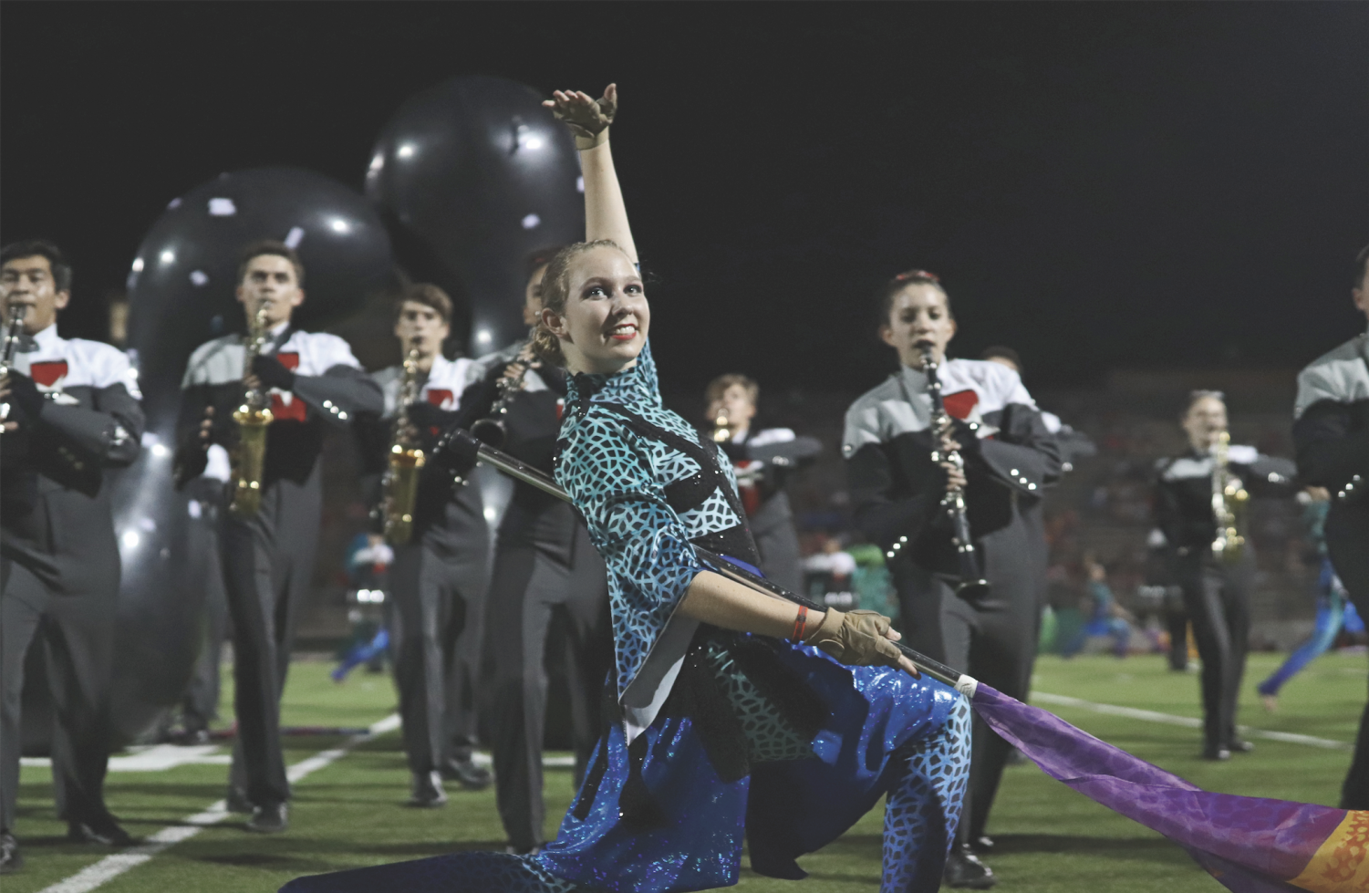 FLEXING ON THE FIELD: Sophomore Emma Taylor shows off her skills during a Bowie football game. Taylor and the girls are planning to travel to Beijing in May for Winter Guard International.