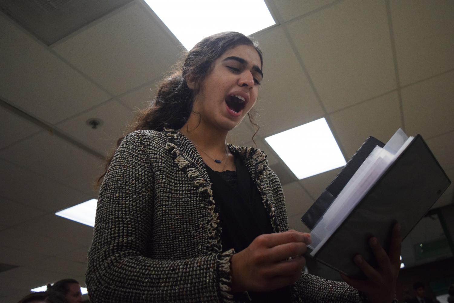 "Making final adjustments during practice, junior Fatema Rehmani prepares for the Randy Pierce Winter Classic at Pattonville High School Dec. 7, 2018. Rehmani competed in Program Oral Interpretation, an event in which students incorporate various selections of literature into a 10 minute performance. ""This year, I explored some different events in speech and debate, and I'm so grateful for all of the various experiences I've gained,"" Rehmani said. ""But I have noticed there are definitely expectations for certain events or debate in regards to whether it's for guys or for girls, which is sometimes limiting and frustrating."""