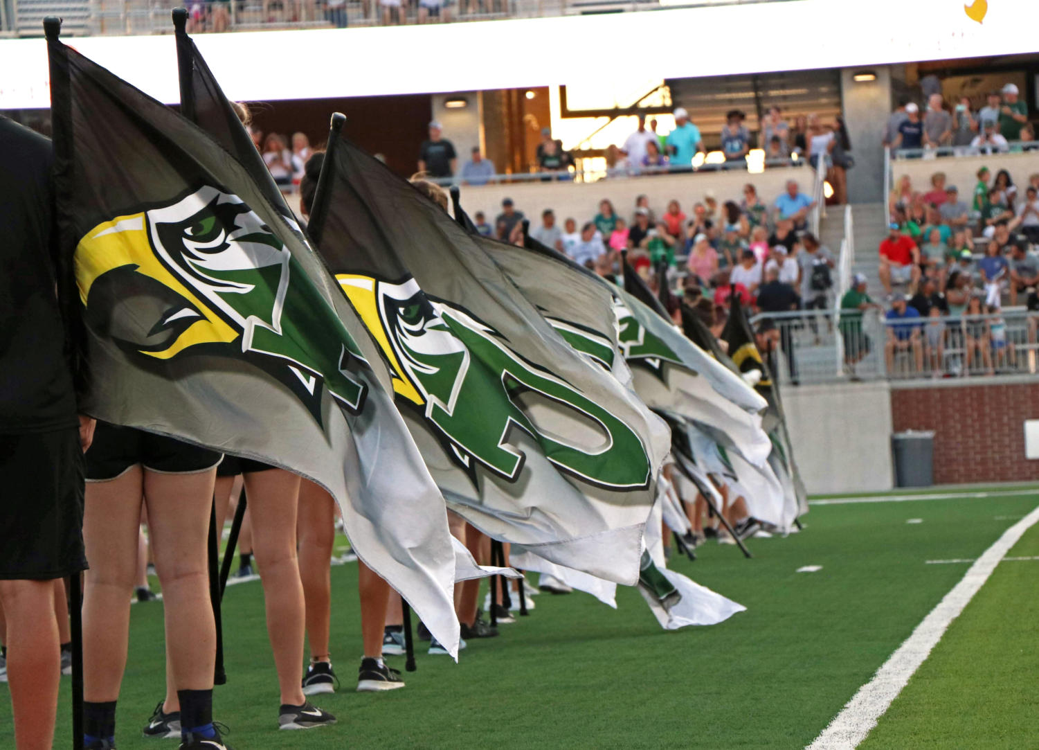 Color guard's flags sway in the wind as they stand in formation. The color guard is a section of the marching band that dances and spins.