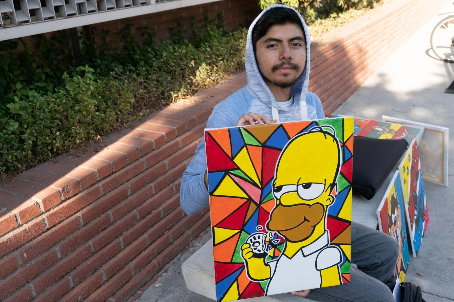 Daniel Galindo displays his artwork on a bench outside of El Camino College's Sherman library on Thursday, Sept.19. Justin Traylor /The Union.