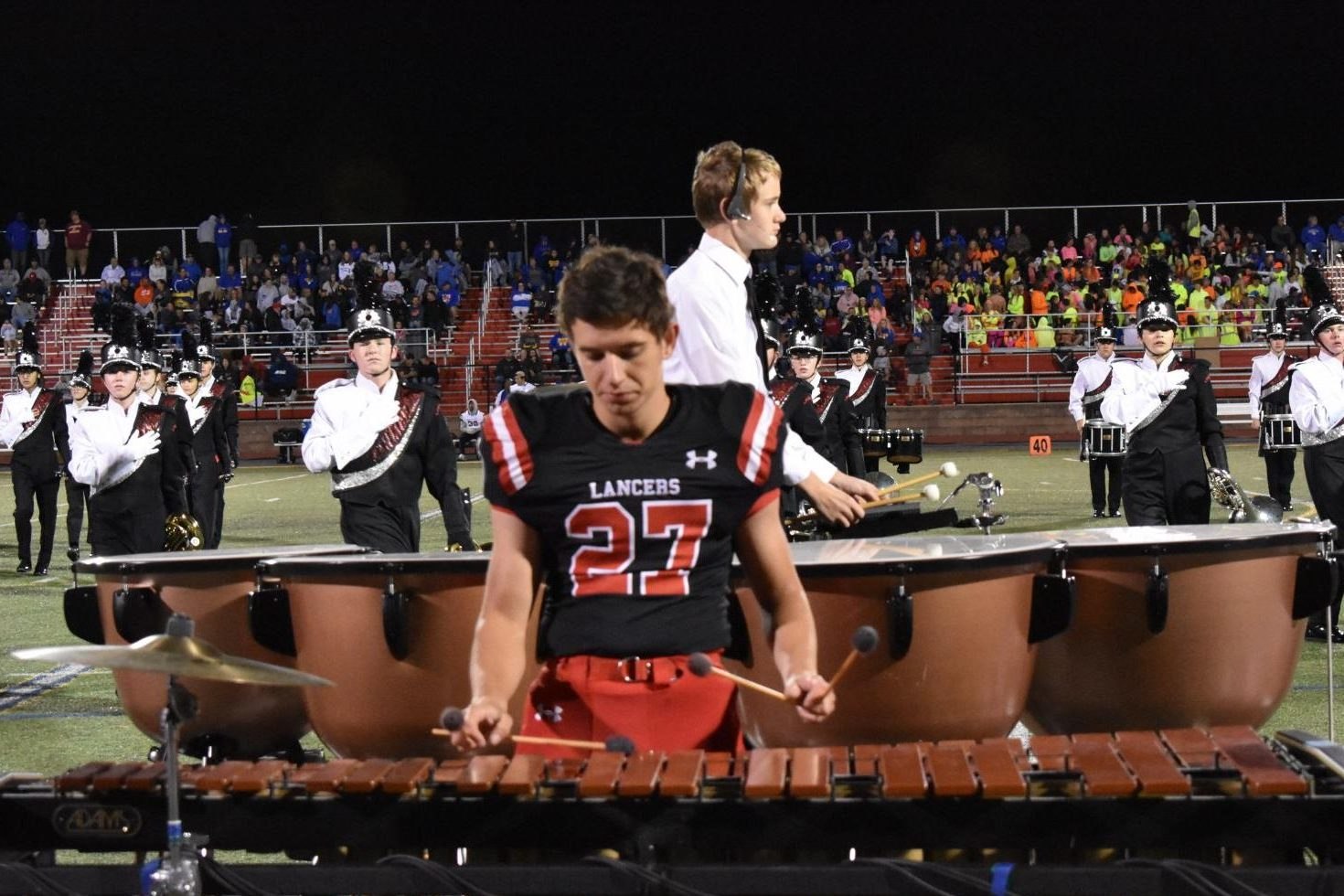 Football player Ethan Blache plays the marimba during the bands half-time performance.