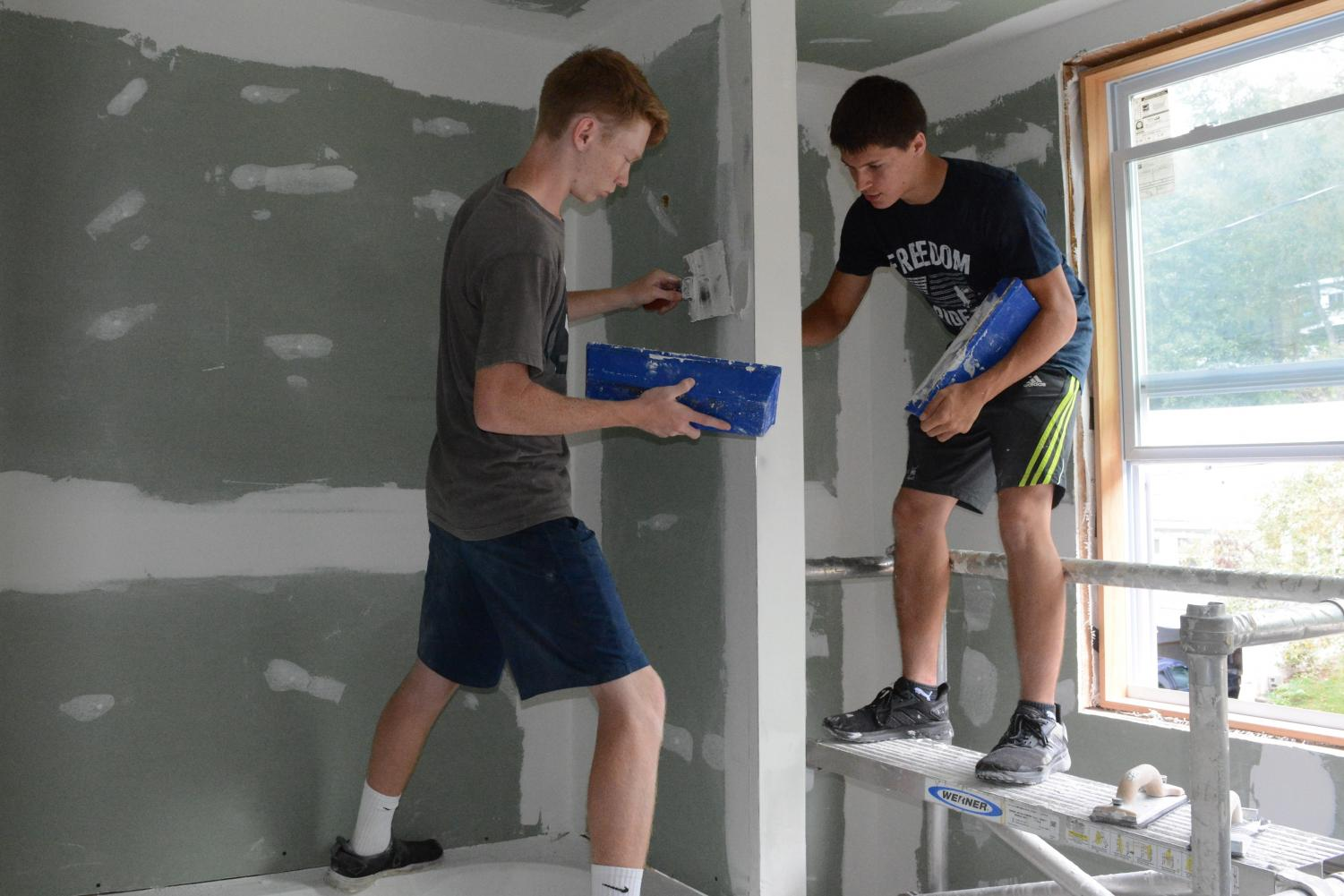 Seniors Zack Neff and Isaac Parks work on finishing the drywall on the TAHS carpentry program house project.