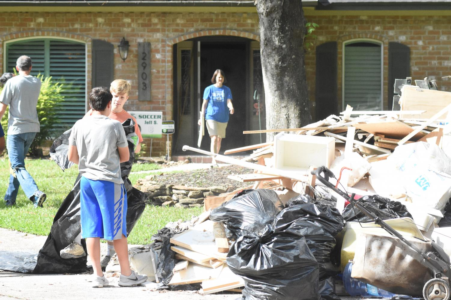 Freshmen Trent Burningham and Nathan Smith add debris to the pile in front of the Smith home, while Tammy Smith carries more woodwork to the trash on Sept. 21.  The Smith family had never flooded in their Bear Branch home before Tropical Depression Imelda hit on Sept. 19.