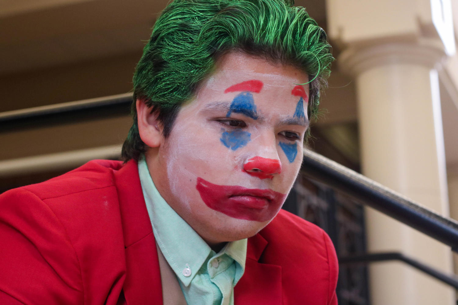 "Senior Erland Merwin poses in his joker costume on the steps to the Auditorium. ""We live in a society,"" Merwin said, quoting one of the Joker's most famous and meme-ified lines. In this column, writer Maddie Moats highlights the many reasons for which she claims the Halloween spirit has died."