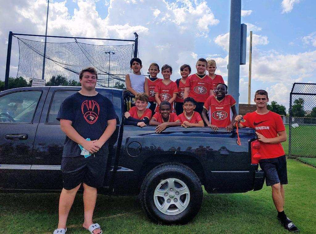Proudly posing with junior Max Roberts' new truck, junior Nolan Steeples , the 49er Farm League  football team, and Roberts take time after a game to celebrate Roberts' coaching skills. The parents gifted Roberts the truck for his dedication to their children.