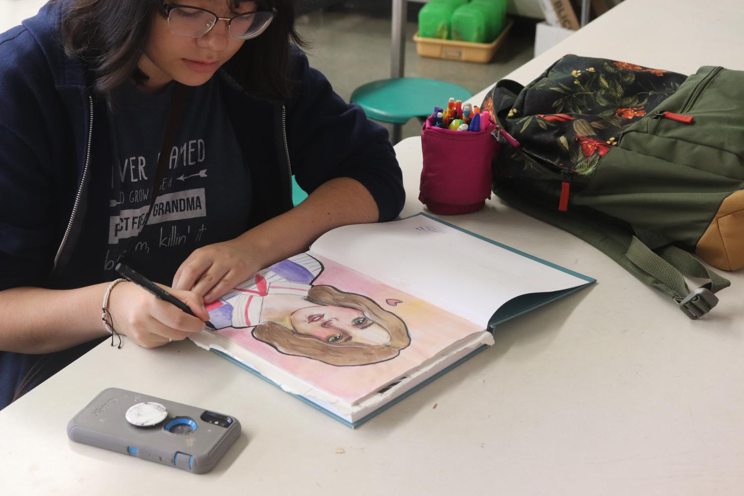 """Sitting in Advanced Studio Art, senior Emily Asplin is working on a side project of a character from the show Stranger Things. Students in Advanced Studio art are allowed to focus on other projects outside of the assigned work.""""Watching shows really inspired me to draw the characters and help develop my style,"""" Asplin said. """"I really like to focus my drawing on people, I am fascinated with the cartoony realistic style and that's what I have developed my style into."""""""
