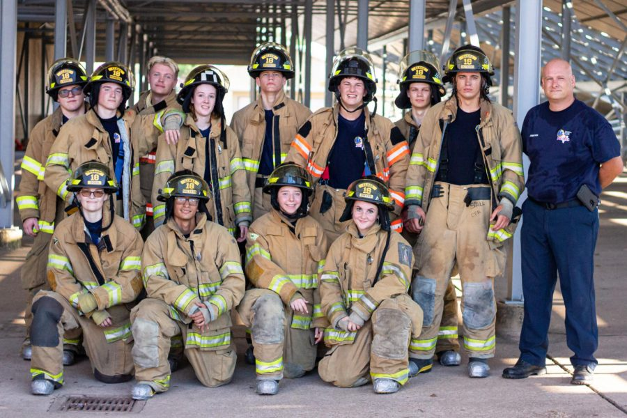The+firefighting+program+gathered+for+a+group+photo+after+practicing+forcible+entry%2C+which+included+multiple+ways+to+pry+open+an+almost+300+pound+door+jammed+with+pieces+of+wood.