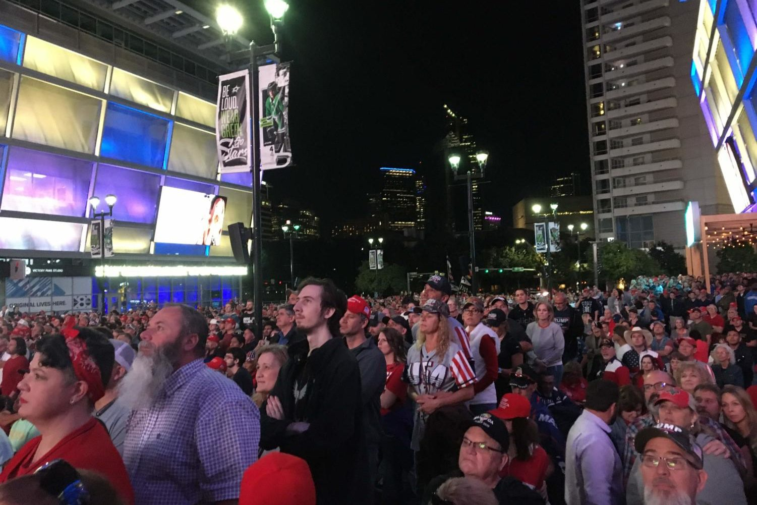 Supporters watch President Donald Trump on a live broadcast in the plaza at the south entrance of the American Airlines Center in Dallas yesterday. Trump held a rally to further his support of the upcoming presidential election.