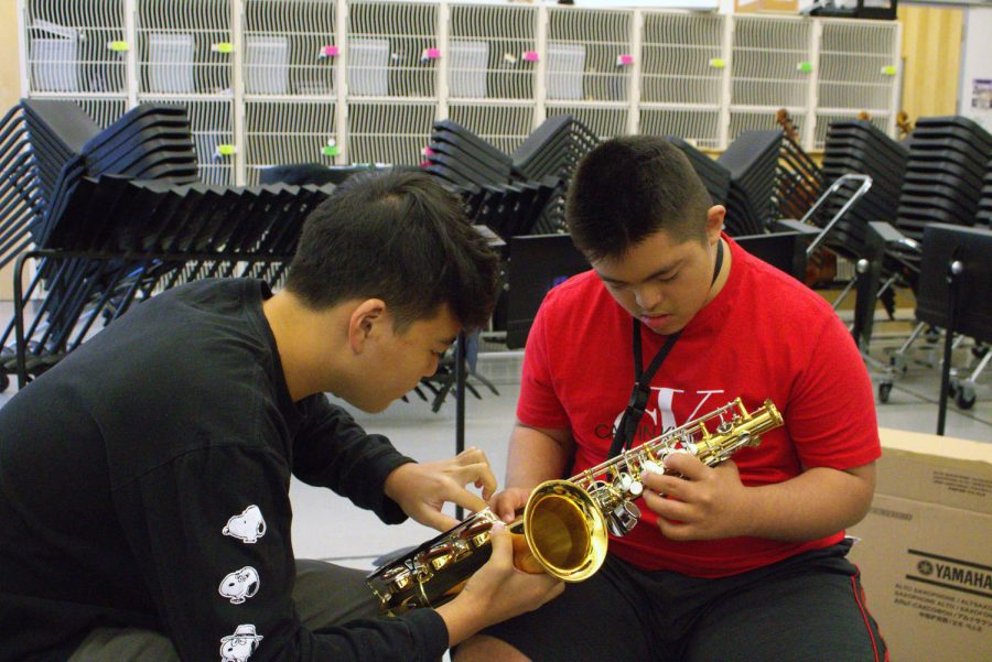 Sophomore+and+mentor+Garrett+Lee+shows+junior+and+mentee+Justin+Silva+where+to+place+his+fingers+on+the+saxophone.+For+beginner+students+like+Silva%2C+memorizing+the+location+and+placement+of+the+many+fingerings+for+the+instrument+can+be+difficult%2C+which+is+why+Lee+must+undergo+training+in+the+form+of+videos+and+books+in+order+to+be+able+to+effectively+teach+his+peers+how+to+play.+