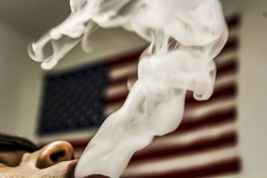 As+a+vapor+cloud+rises+in+the+air%2C+an+American+flag+hangs+proudly+behind+it.+With+47+states+already+having+restrictions+such+as+no+indoor+vaping%2C+people+are+showing+initiative+to+make+a+change+in+the+nation.+Massachusetts+has+even+took+steps+further+and+banned+the+sale+of+all+vaping+products+for+four+months.