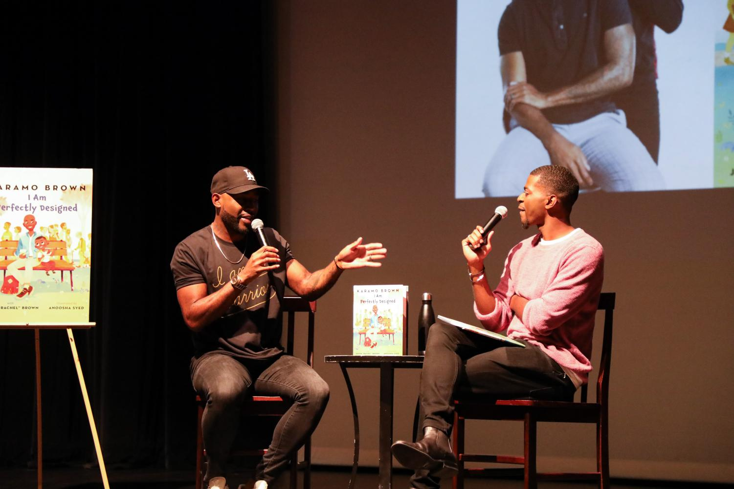 """Karamo Brown (left) and Jason """"Rachel"""" Brown (right) talk to an audience in the Eagle Theater about their new picture book, """"I Am Perfectly Designed."""" The father-son duo pulled from their own experiences and relationship to write a heartwarming story with an important message about self-confidence."""