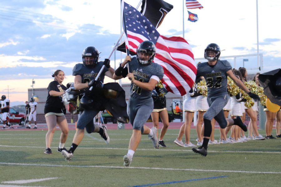 "Kade Ramsey '20 and Sean Hicks '20 burst through the homecoming banner and sprint on to the field at Echo Park for the Homecoming Game Sept 19. This game against Arapahoe High School ended with a score of 24-12. ""We're losing the game so far, but our school spirit is strong,"" Shwetha Suresh '22 said."
