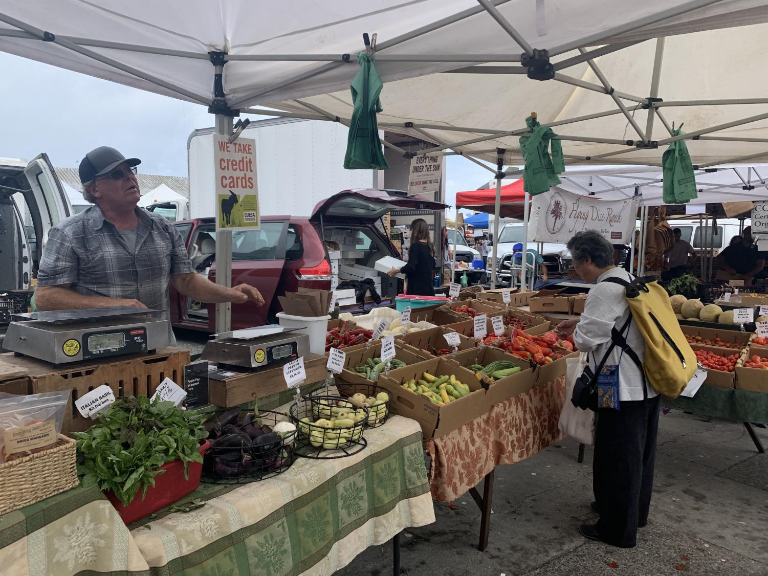 Farmer Bill Crepps of the farm Everything Under the Sun sells his dried fruit to a customer at the Ferry Plaza Farmers Market. Crepps farms his fruits and vegetables using sun-drying methods that achieve organic status and employ sustainable methods.