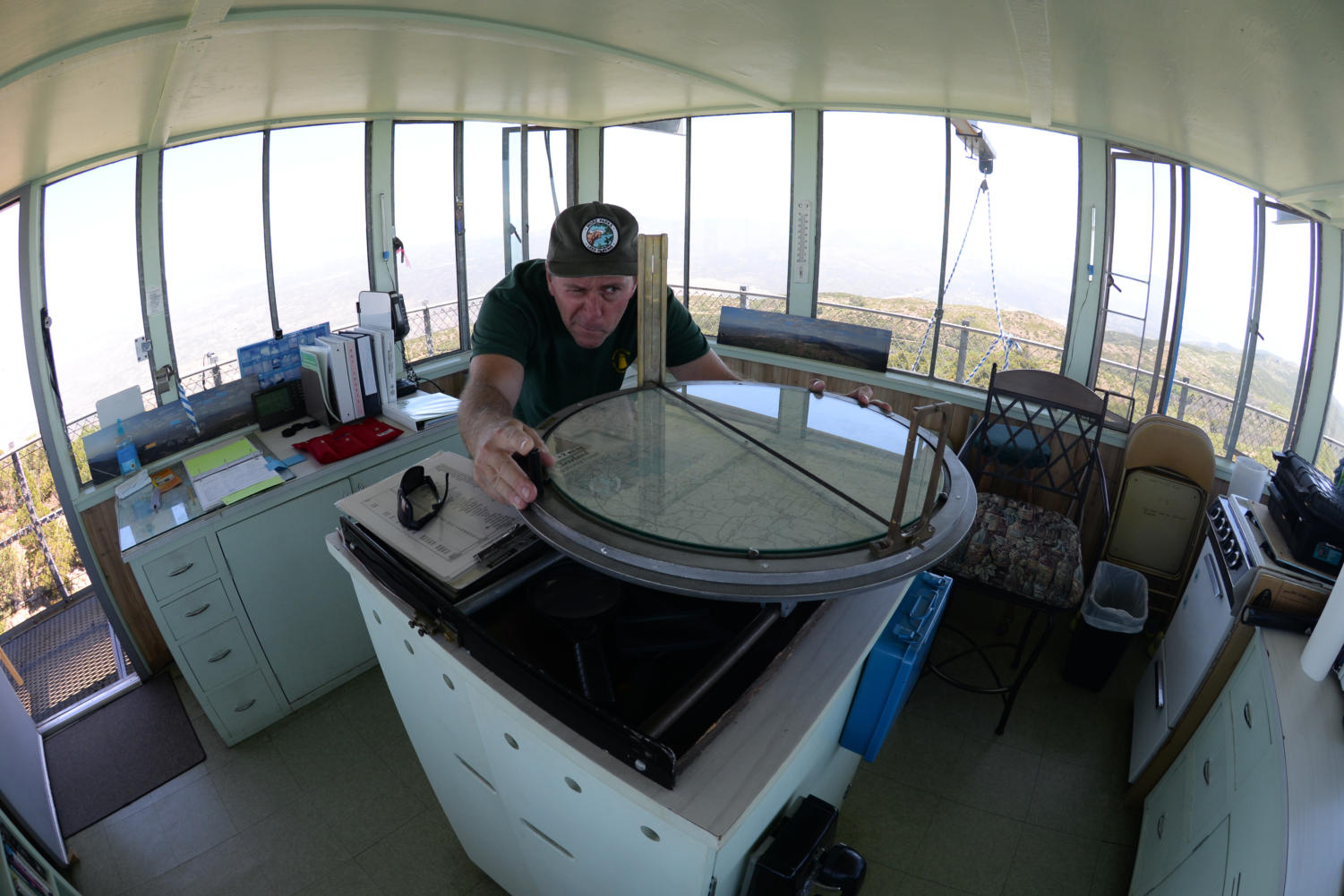 Using the Osborne Fire Finder, volunteer lookout Bill Kaiser determines azimuth (direction in degrees) and distance from the tower of smoke or lighting downstrikes. This information is radioed to Cleveland National Forest who can deploy ground crews, helicopters or air tankers to fight the fire. The Osborne fire finder was developed in 1914 and still used in towers today.