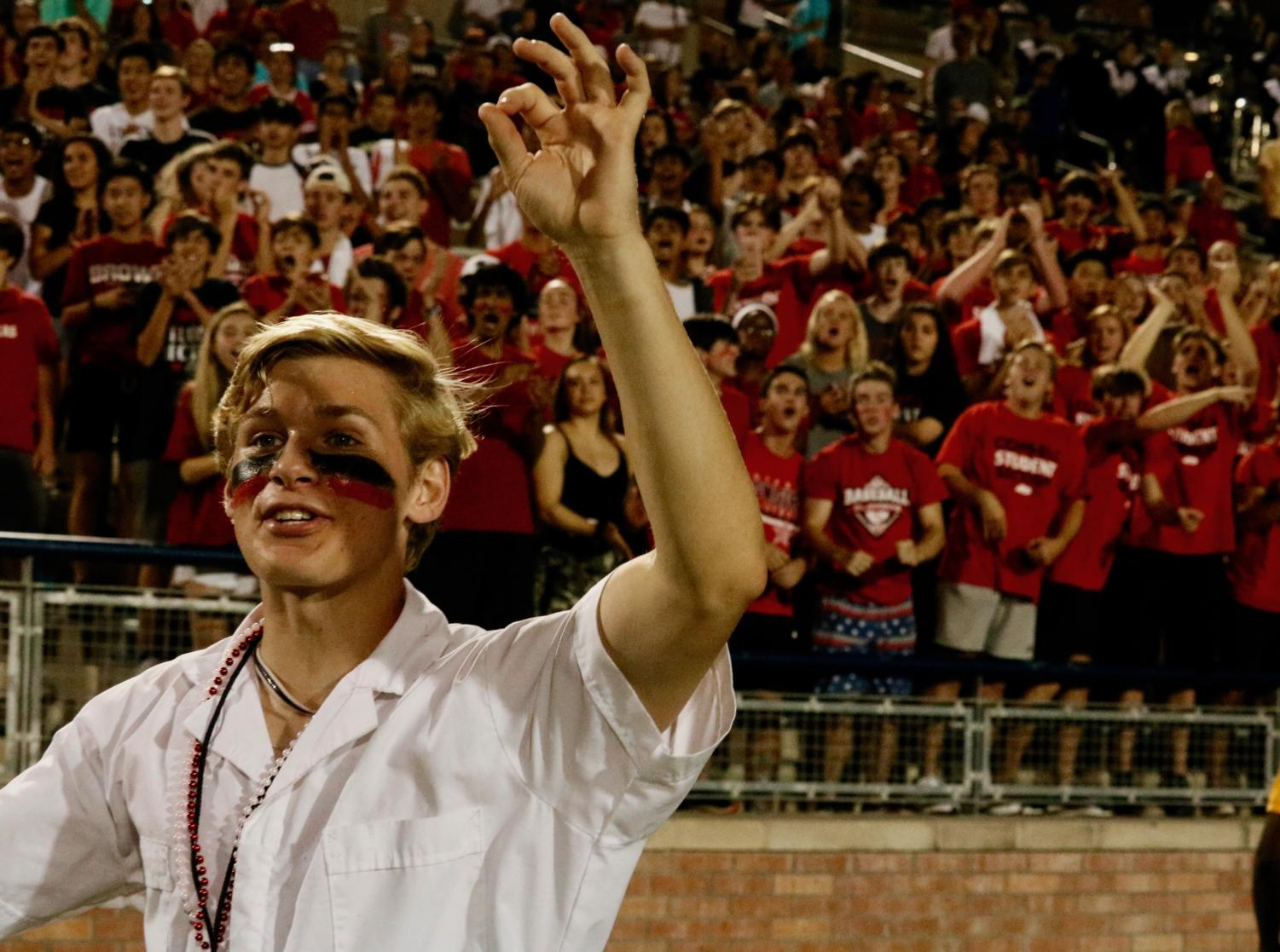 Coppell High School senior plunger boy Leo Swaldi holds up a third down sign during Coppell's game against Allen on Sept. 13 at Eagle Stadium. Swaldi takes rigorous academic courses and is the senior class president in addition to the plunger boy.