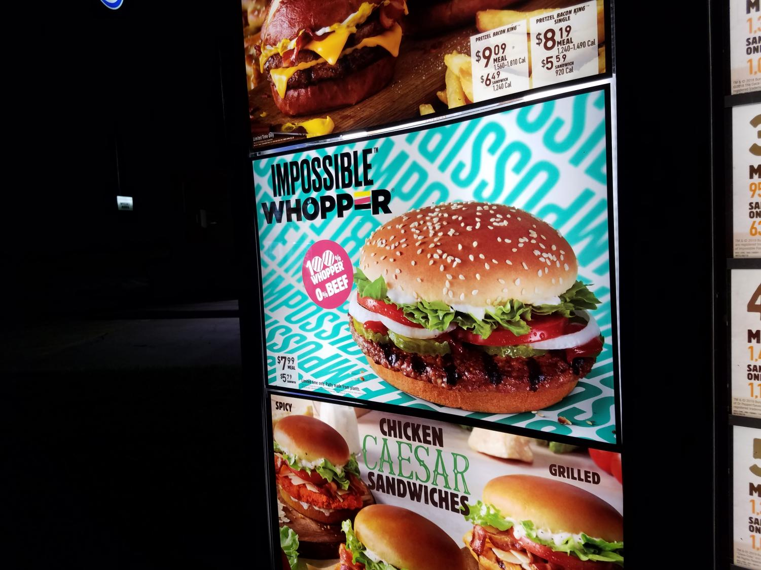 Burger King's outside menu boasts a large section showcasing the new Impossible Whopper alongside its traditional meat-based burgers.