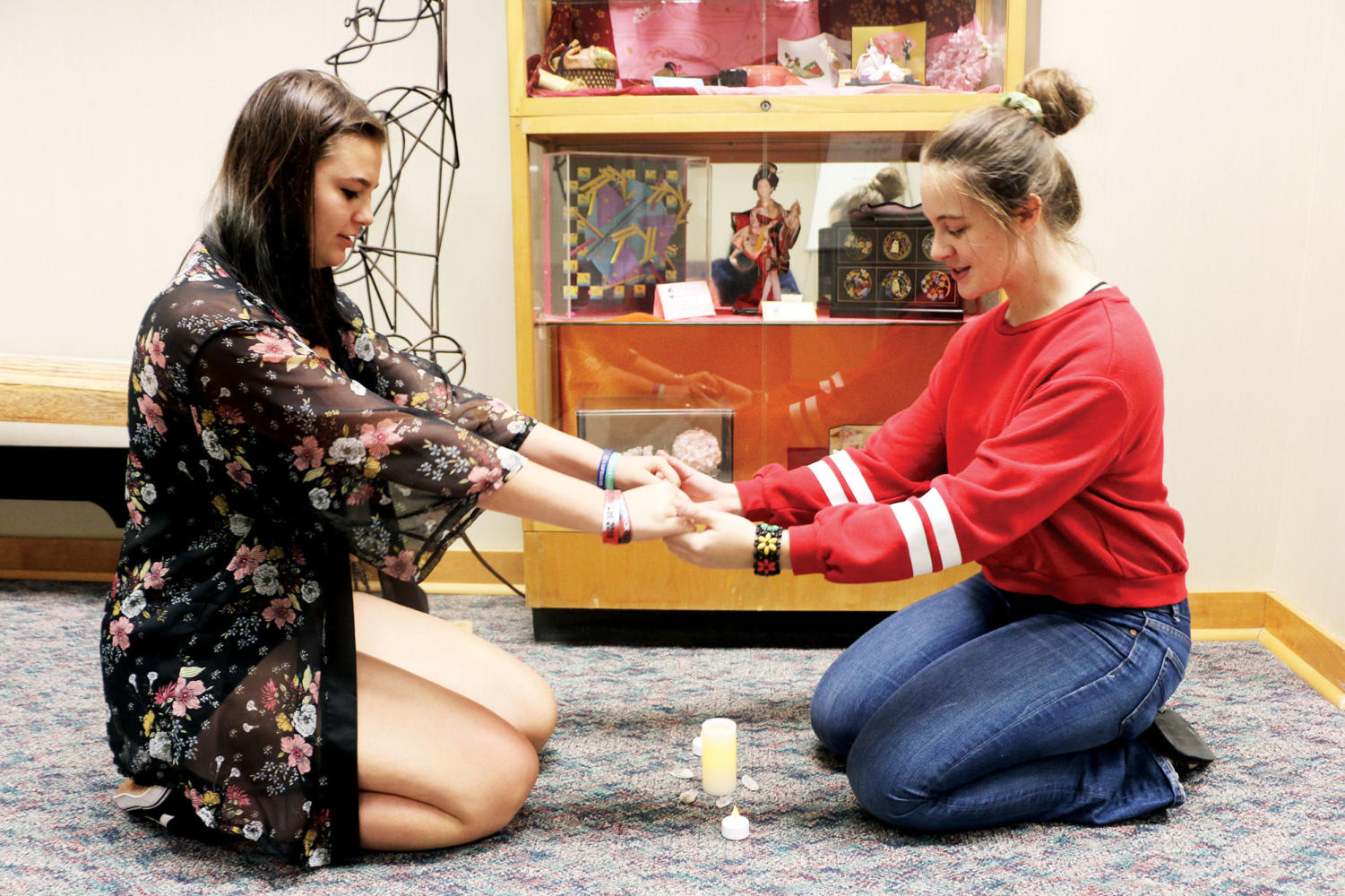 """Juniors Olivia """"Via"""" Sargent and Skylar Greaves hold hands over a pentagram of crystals. Greaves said that Wiccan practices channel a more spiritual and earthy aspect  of witchcraft."""