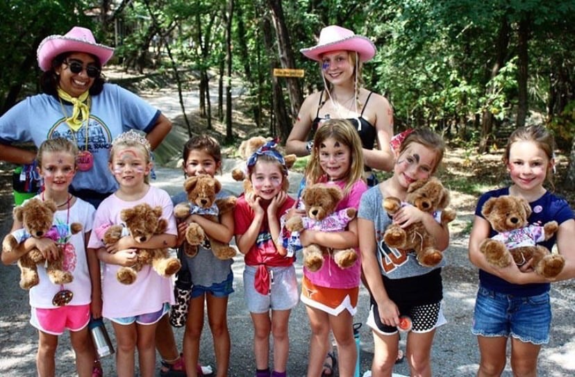 Catie+Mendivil+poses+with+a+fellow+counselor+and+her+troupe+of+campers+at+a+girls+summer+camp+in+Wimberley.+Mendivil+enjoys+spending+her+summers+with+kids.+%E2%80%9CI+never+was+a+person+who+thought+I%E2%80%99d+love+spending+time+with+kids%2C+but+I+think+it%E2%80%99s+fun%2C%E2%80%9D+Mendivil+confesses.+%E2%80%9CI+would+encourage+people+who+want+to+like+babysit%2C+or+get+involved+with+kids%2C+to+do+it.+It%E2%80%99s+really+fun%2C+and+kids+are+hilarious.%E2%80%9D+Photo+courtesy+of+Mendivil.