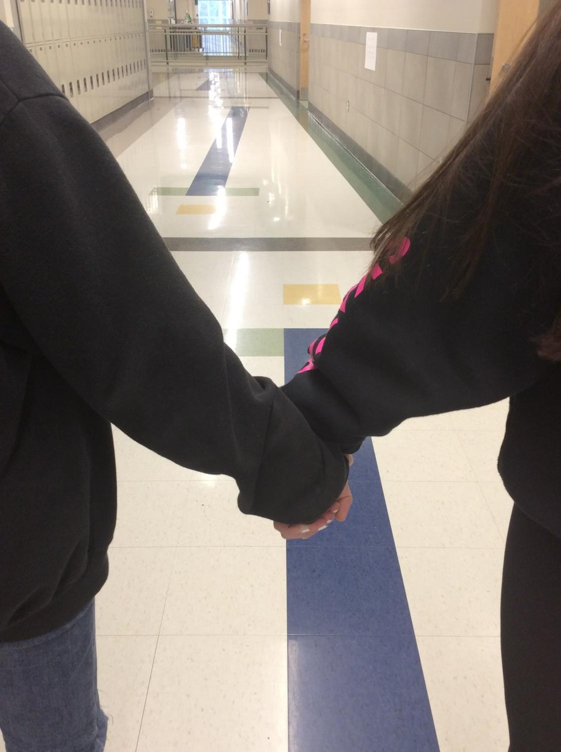 Two students at Abington High School hold hands in the hallway on Friday, December 6, 2019.