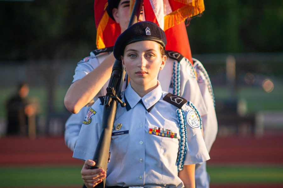 Senior+Emma+Eidmann+presents+the+colors+alongside+other+AFJROTC+students%2C+representing+the+Marauders+prior+to+the+Homecoming+football+game.