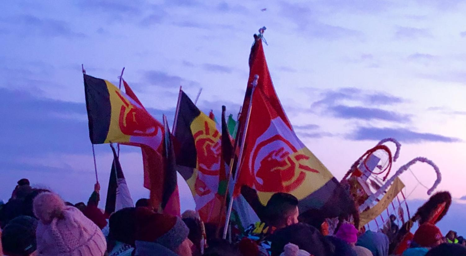 The Red Nation flag and AIM banner fly high in front of the San Francisco Sunrise. Organizers asked all attendees not to photograph the dancers out of respect for them praying.