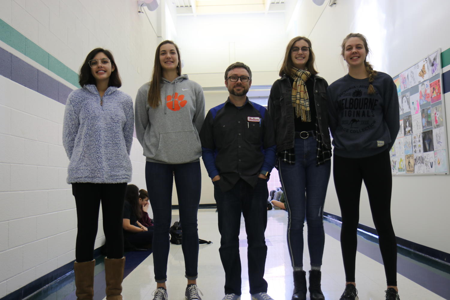 Zoë Malik, junior, stands on the left next to Ally Fitzgerald, sophomore. Katie Weiss, senior, poses on the far right, with Kira Mangan, senior, on the left of her. Ed Bolton, chemistry teacher, is 5' 7