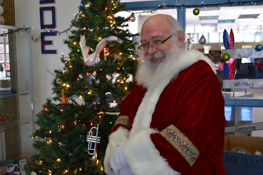 "Mr. David Springstead, dressed as Father Christmas, stands in front of the Christmas tree set up in the foyer. It previously displayed the bulbs for ""Be a Santa to a Senior,"" which was sponsored by Kempsville's security team."