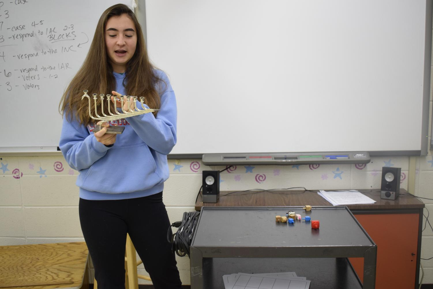 """Pointing to the fourth branch on the Chanukiah, junior Ella Seigel describes Chanukah and other Jewish holidays to her peers. Seigel presented with props to share part of the Jewish culture with students at Westminster. """"Their engagement showed that if you open up and show your differences, that can also provide unity in understanding,"""" Seigel said."""
