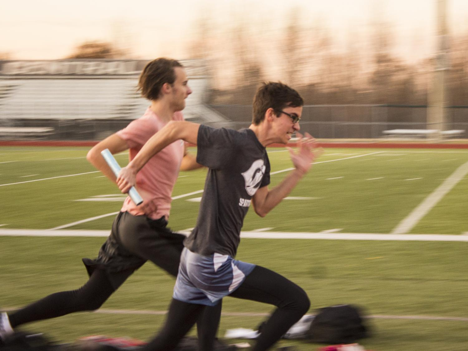 """OFF-SEASON SPRINTING: Eli Allen and Reed Easterling perform handoffs with a baton. """"My biggest goal is just to stay in shape and to get myself better so that during track season I can get better and better times,"""" Easterling said."""
