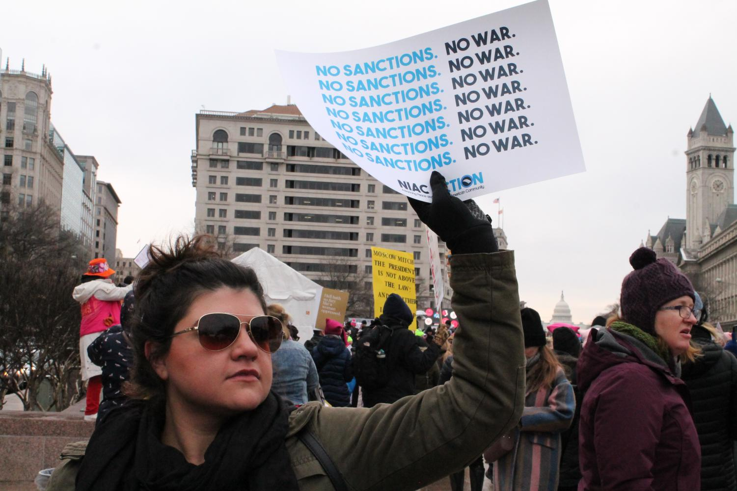 A protestor holds a sign declaring peace and no war before the Women's March starts.