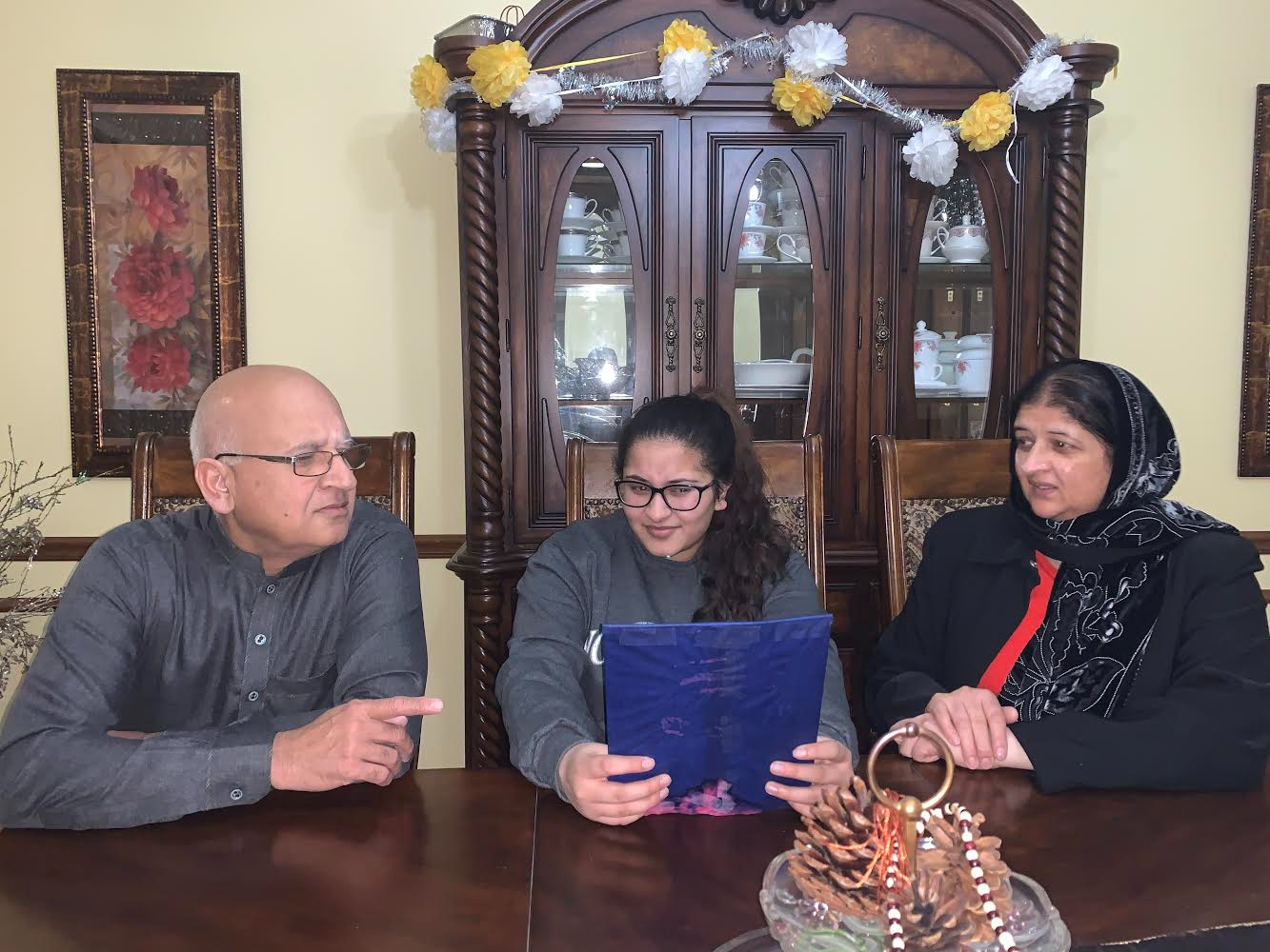 """Senior Umeera Farooq goes through college application papers with her parents at the dinner table. Farooq's parents, who immigrated to America, struggled with assisting her through the application process. """"My parents have not attended college, and I'm a first-generation college student,"""" Farooq said. """"it's gotten easier especially because I know now I've grown so I can help myself."""""""