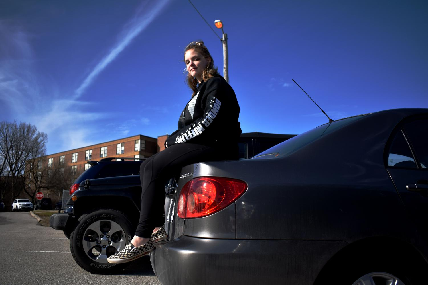 "Junior Michaela Linden sits on the trunk of her car. She now has her license, but there were a few instances in the weeks following the accident that Michaela needed to walk home. ""The rest of last year I walked home a total of three times after I got hit, and every time I had a panic attack,"" Michaela said. ""It was very soon after [the accident] and I was still very on edge about it. I got rides from friends when I could, or I had parents pick me up."""