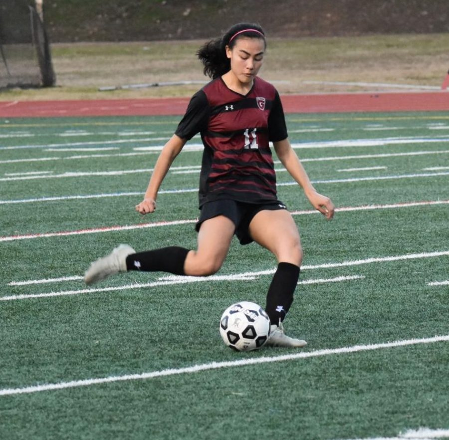 Mia+Wood%2C+who+is+now+playing+college+soccer%2C+takes+a+free+kick+in+a+game+against+North+Atlanta+last+season.+Soccer+tryouts+started+Jan.+13+for+this+season.