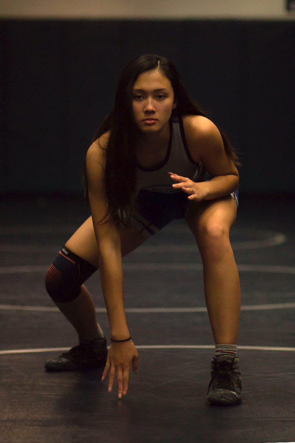 FACE OFF: Sophia Tran takes her stance as she would for the start of a match. Being the only female wrestler who competed last season, the senior sets and example for the new members.