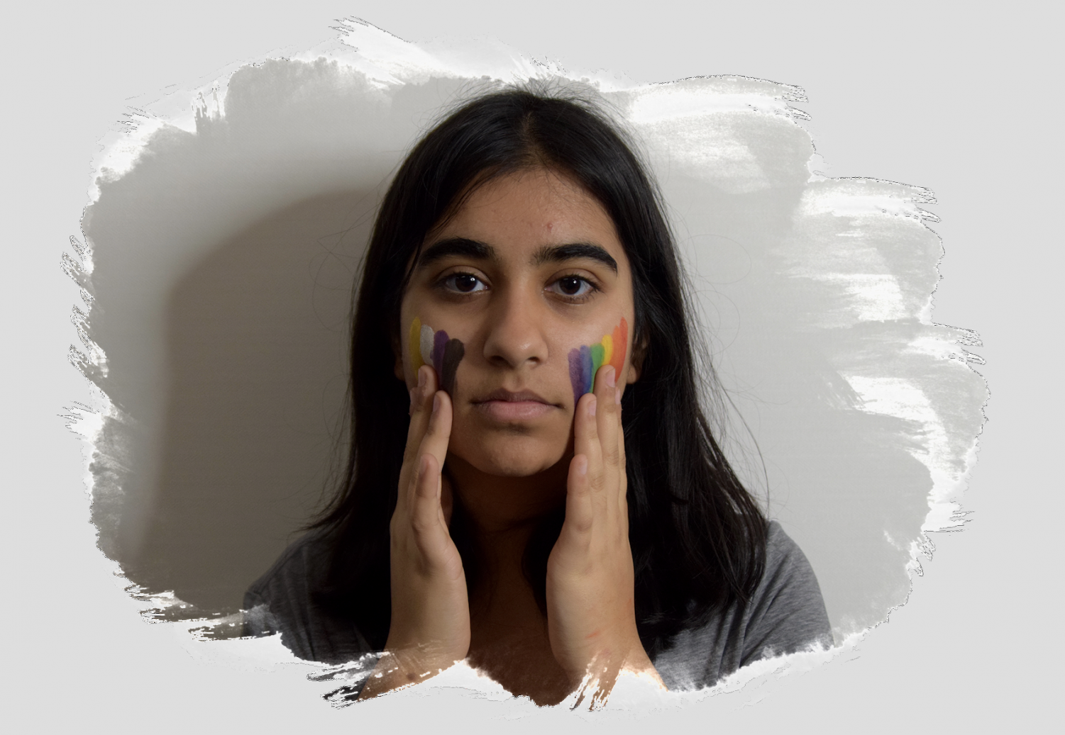 Sophomore Anika Sharma drags face paint down their face, using the colors of the non-binary and LGBTQ flags.