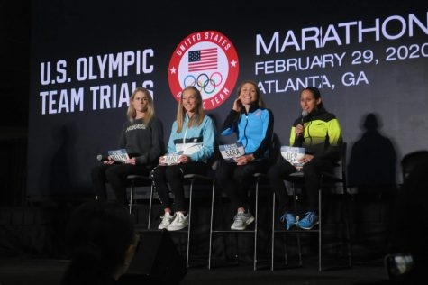 Left to right: Top seeded runners Kellyn Taylor, Emily Sisson, Sara Hall and Des Linden sit onstage as Linden answers a question from a high school runner in the crowd. Linden finished second at the 2016 U.S. Olympic Team Trials – Marathon in Los Angeles, qualifying her for the Rio Olympic Games.