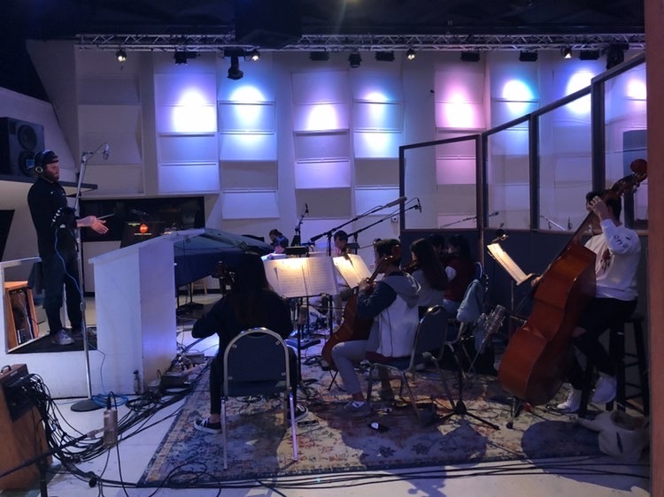Music+teacher+Desmond+Stevens+conducts+the+members+of+the+orchestra+as+they+record+in+the+studio.+In+studio+recordings%2C+the+musicians+have+to+both+follow+the+conductor+and+listen+in+the+headphones+for+the+metronome+and+cues.