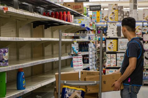 Jonathan Jacquez, Walmart employee and high schooler, tries to stock chemical cleaning products in an aisle half empty due to customers panic buying.