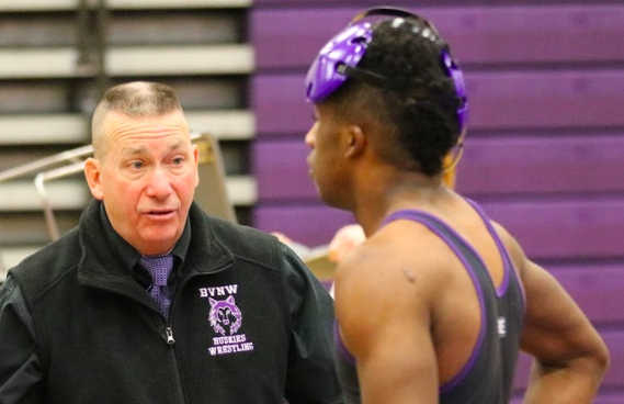 Head coach Tim Serbousek talks with senior wrestler Edward Thomas during a dual on Jan. 15 at BVNW. As the head coach for 27 years, Serbousek holds a 426-182-1 record as head coach. Former athletic director Steve Harms said that Serbousek knows what it takes to be a successful head coach and has the correct priorities for his team.