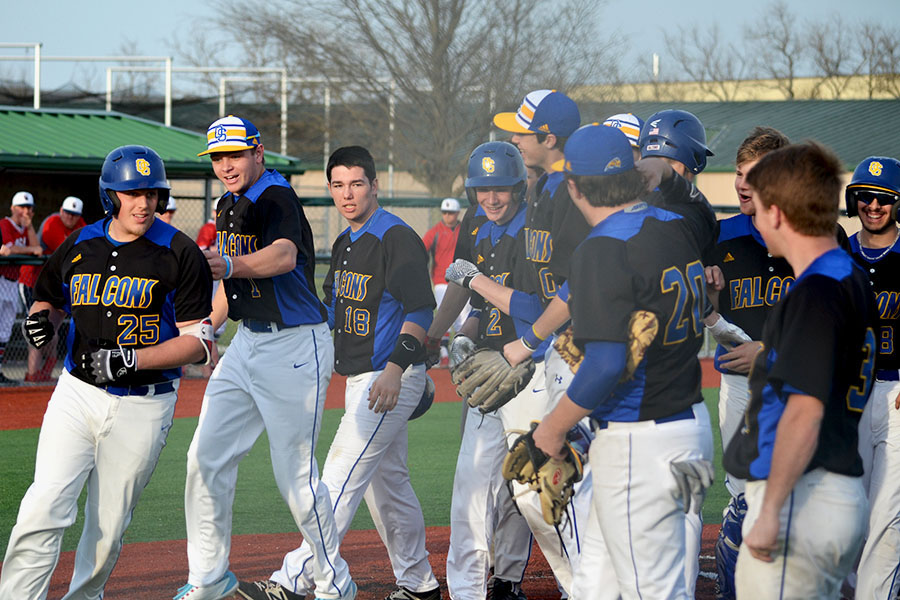 The+baseball+team+returns+to+the+dugout+after+celebrating+a+home+run+against+Olathe+North.+It+was+announced+on+March+18+that+there+would+be+no+fireworks+this+year%2C+however%2C+as+all+spring+sports+have+been+canceled+in+their+entirety.