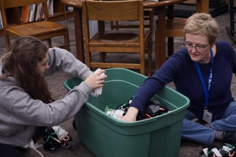 BOUNTIFUL BINS:  Junior Rachel Plotkin and sponsor Jane Farmer move decorated socks into the bin for the NHS sock drive. The prepared socks were then taken to homeless shelters around Austin. Photo by Isabella Dietz.