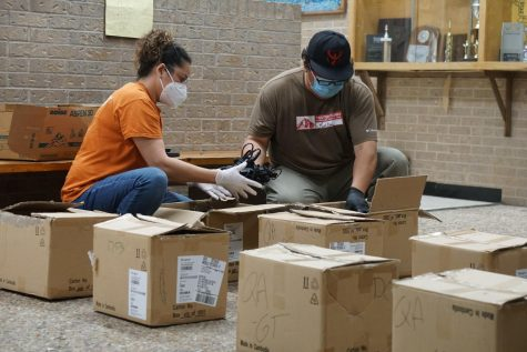 Ana Rosa Tenorio and Ivan Ramos, Austin ISD transportation employees based at Nelson Field, unpack Chromebook chargers to be bundled with Chromebooks at Anderson High School. Anderson is one of five locations hosting curbside computer services Monday through Friday from 9:30 a.m. until 3:30 p.m. Curbside computer services are also available at Austin and Crockett high schools and at the AISD Performing Arts Center. Photo by Dave Winter.