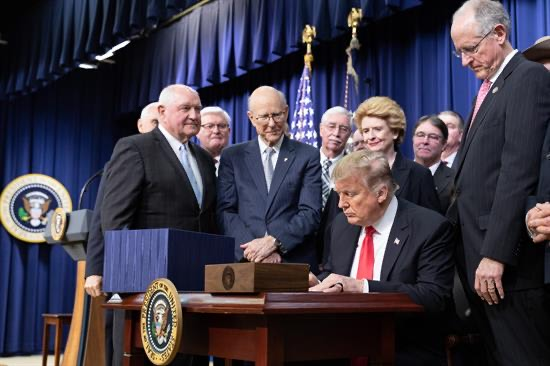 President Trump on Dec. 20, 2018, signs the 2018 Farm Bill in Georgia while surrounded by national and state level officials.